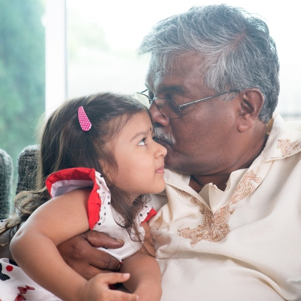 Grandfather kissing granddaughter on forehead | thegoodstuff