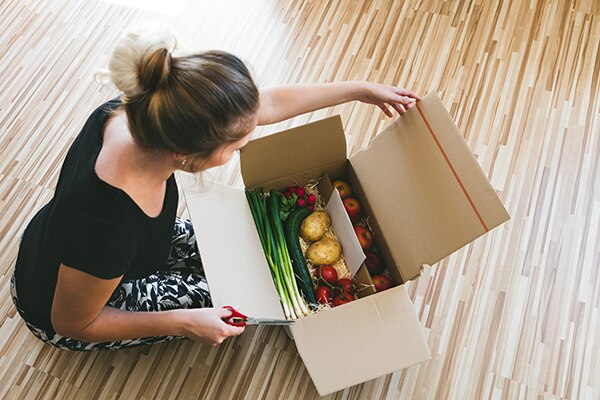 woman opening package of grocery delivery