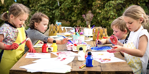 Kids painting at a craft table outside