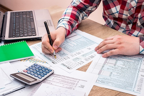 Man filing taxes using tax software, calculator and forms