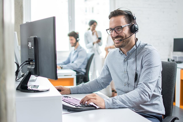 Customer support operator with headset on computer