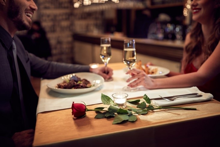 Couple enjoying a romantic Valentine's day dinner at restaurant with champagne and roses.