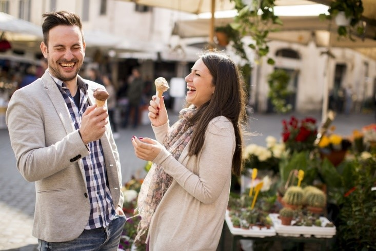 Couple on Valentine's Day date laughing and enjoying ice cream cones.