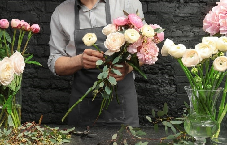 Male florist putting together white and pink flower arrangement